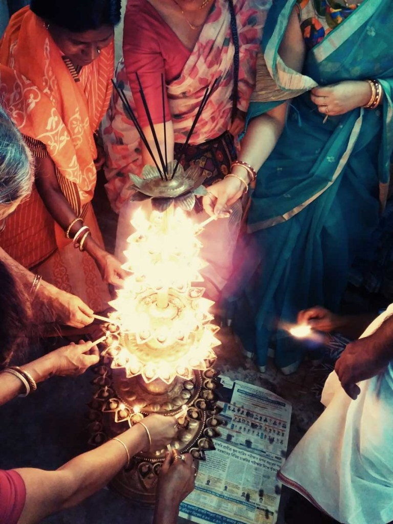 lighting 108 diyas during Durga Puja