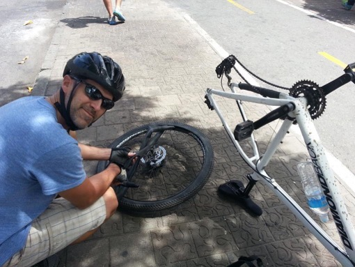 Al McCullough fixing his flat tire in Medellin