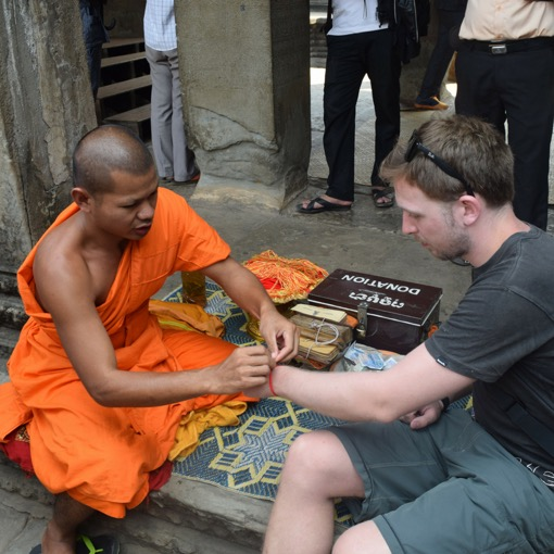 Kev of Two Tall Travellers Receiving a Wristband from a Monk at Angkor Wat
