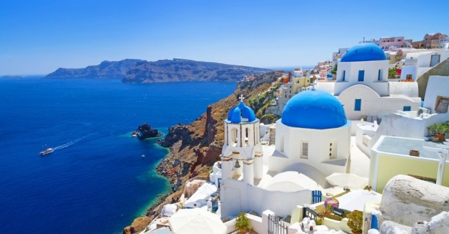 Come explore Santorini, Greece - where the brilliant blue waters of the Mediterranean stretch from the rocky cliffs and glimmering white buildings above.
