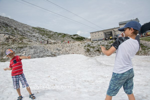 Roman and Andrey are playing with the snow in sandals near Krippenstein cable car station