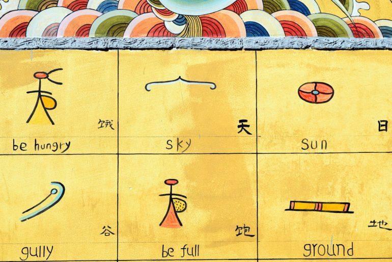 בנייני העיר העתיקה מקושטים בכתב הדונגבה העתיק (צילום: טל ניצן)