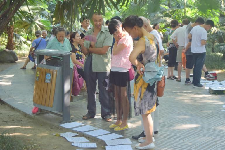 עוברי אורח בודקים את המודעות בפארק העם בצ'נגדו (צילום: טל ניצן)