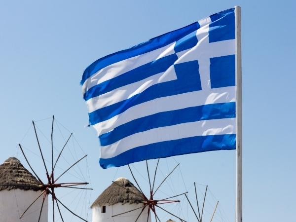 Bandiera della Grecia che sventola con sfondo dei mulini