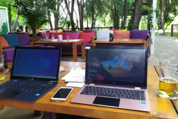 What is a Digital Nomad? - Two laptops, mobile phone and beers on a table in an outdoor restaurant