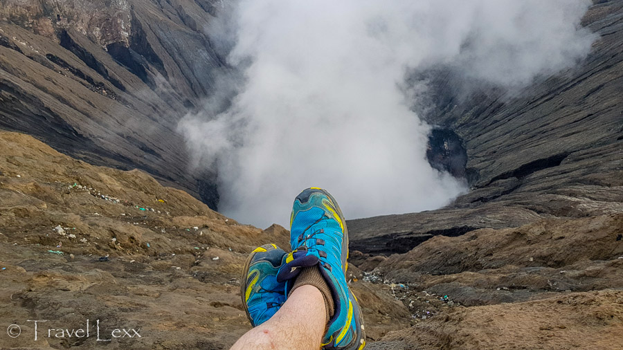 Dangling feet over the crater of Mount Bromo, Java, Indonesia