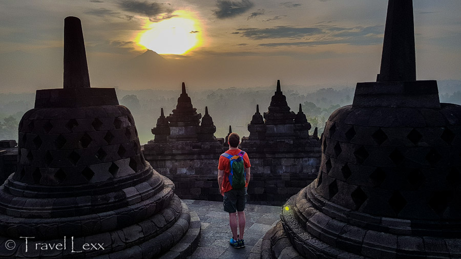 A man standing amidst stupas at Borobodur at sunrise