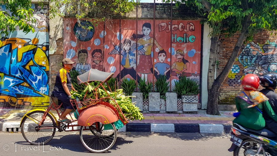 A man pedalling a cart laden with produce through a city