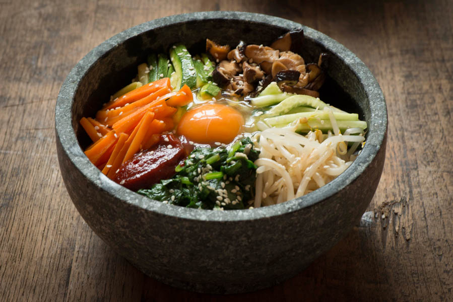 A Korean stone bowl called a dolsot on a table with food inside