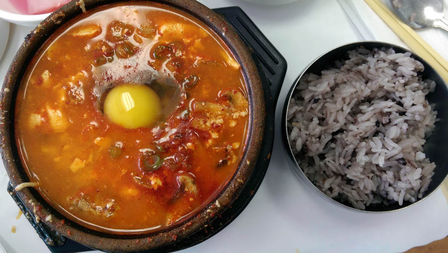 A hotpot of a spicy soft tofu stew next to a small bowl of rice