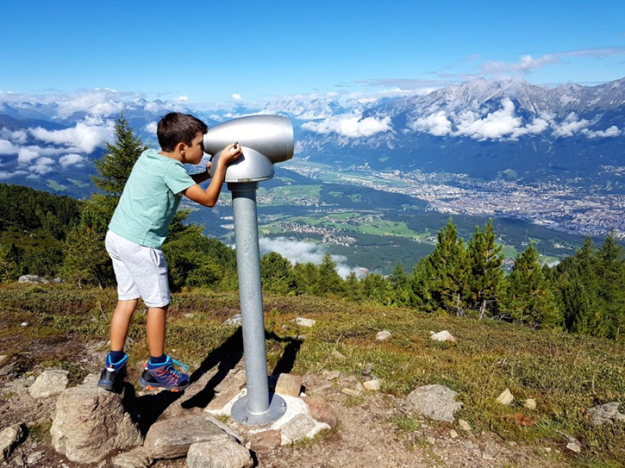 A young boy looking into a binoculars on a mountain trail overlooking a valley near Innsbruck, Austria