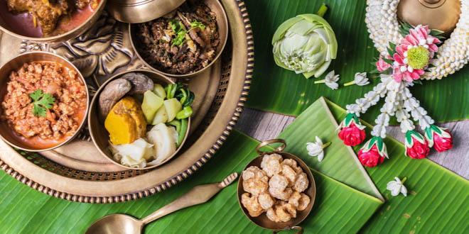 Thai snacks including pork curry, chilli dip, minced pork salad, soft boiled vegetables and pork snack served in brass dishes.