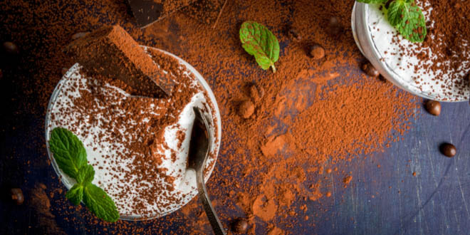 Traditional tiramisu dessert, one of the most famous Italian dishes, decorated with cocoa and mint leaves.