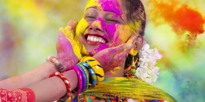 Fun, Food and Festivals in India. Portrait of a young Indian woman celebrating the Holi color festival.