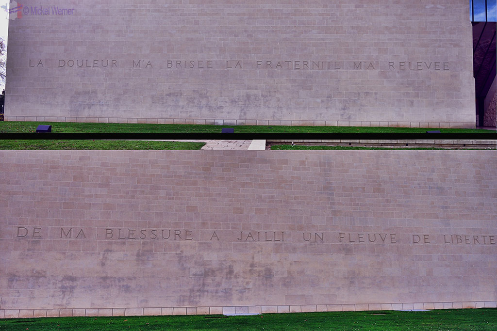 Two outer walls of the Caen WWII Memorial and its proverb