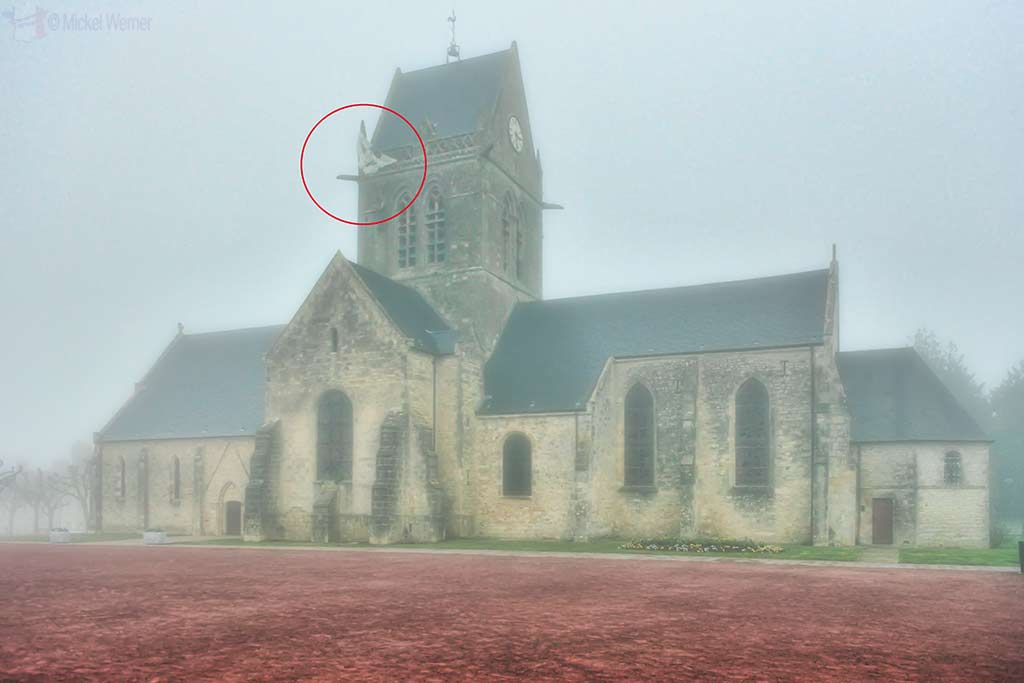 Famous church with parachute hanging off tower of Sainte-Mere-Eglise in Normandy