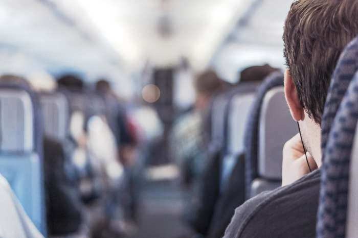Man on a plane listening to music.