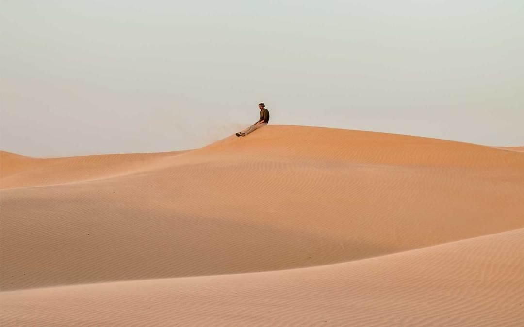 Man on desert hill in Oman