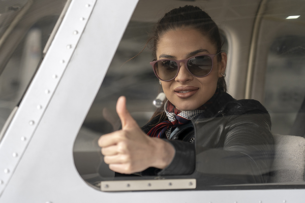 Young Woman Pilot Looking Through The Cockpit Window and Giving Thumb Up
