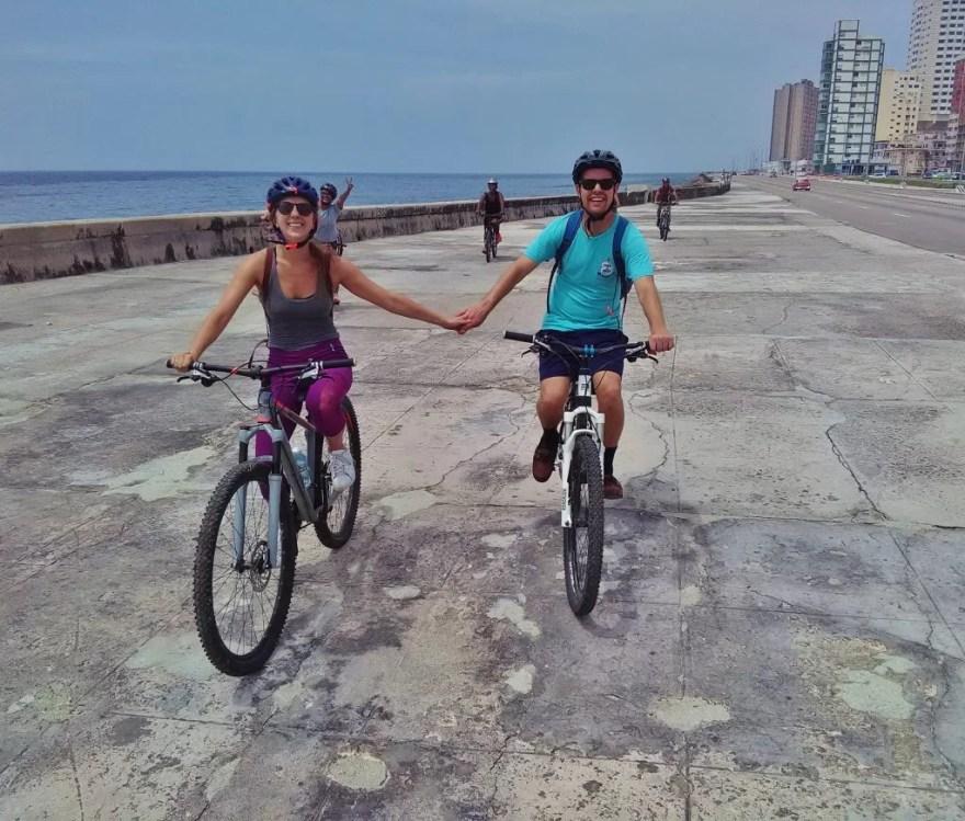 Brandon and Erin from Traveling Atlas biking on the Malecon in Havana, Cuba.