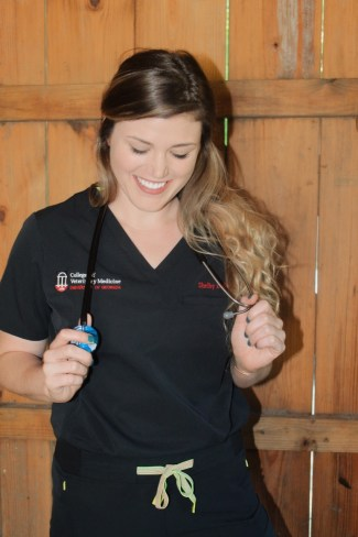 Veterinary Student wearing Medelita scrubs in black with the UGA College of Veterinary Medicine embroidered on the top.