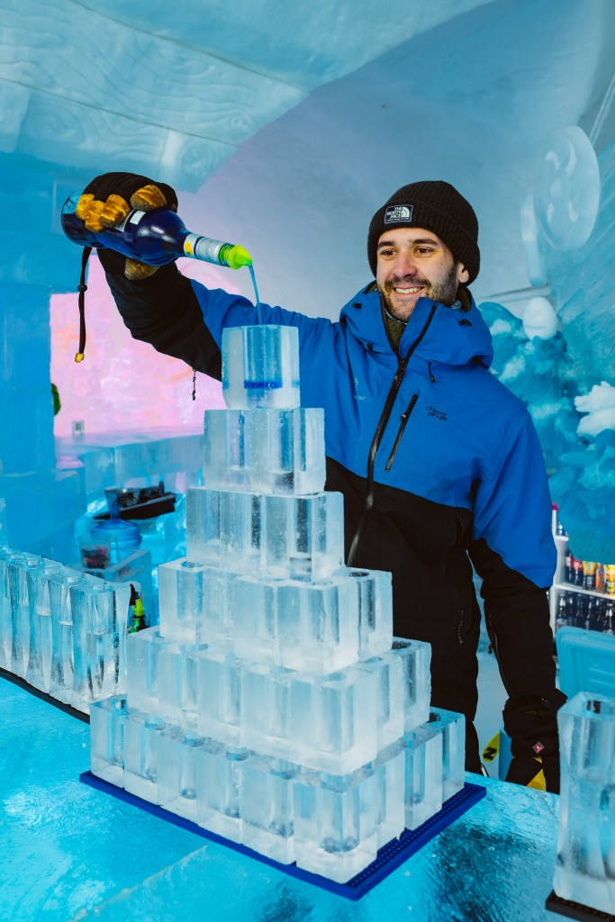 Handsome bartender serves in frozen ice glasses at Hôtel de Glace (Ice Hotel) in Québec
