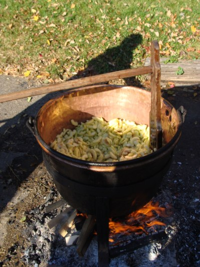 Making old fashioned apple butter kettle fire wooden spoon