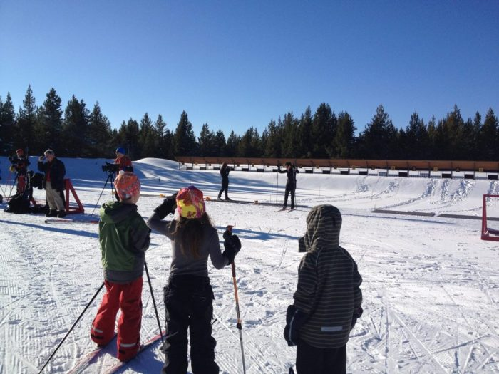 Budding Nordic skiers watch participants learn to shoot at the Rendezvous Ski Area biathlon course.