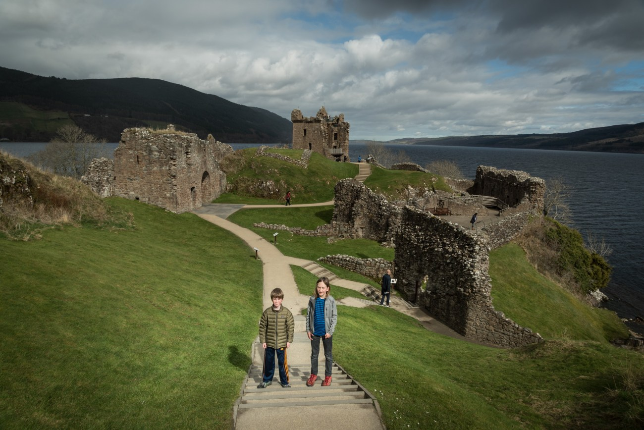 two kids with Urquhart Castle and Loch Ness in the background