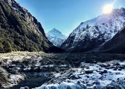 Snow covered mountains and ground during a bright sunny day in Fiordland National Park, NZ