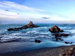 Rocks near the beach surrounded by the Pacific Ocean during twilight off the coast of New Zealand