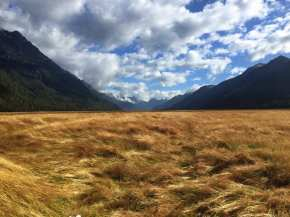 Valley in Fiordland National Park with clouds and mountains in the background