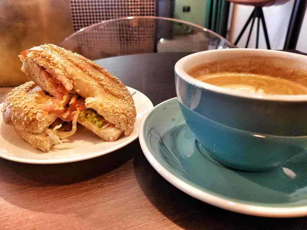 Flat white in turquoise mug alongside a prosciutto and tomato bagel sandwich.