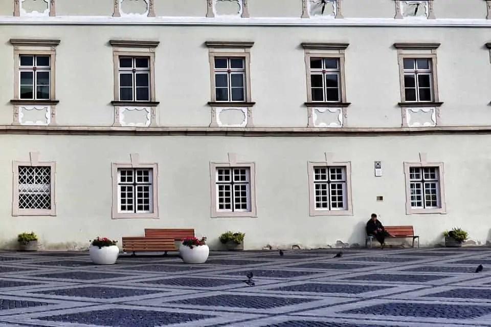 Man sitting alone on bench in an empty Piata Mare in Sibiu, Romania