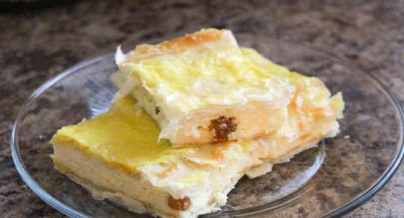 A few squares of cheese pie on a crystal plate, a traditional Romanian dessert.