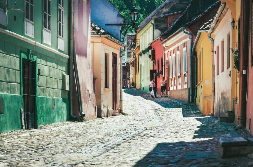 Winding cobbled street in Sighisoara flanked by colorful buildings.