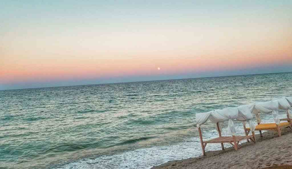 Beach beds on the shore of Vama Veche, Romania during moonrise.