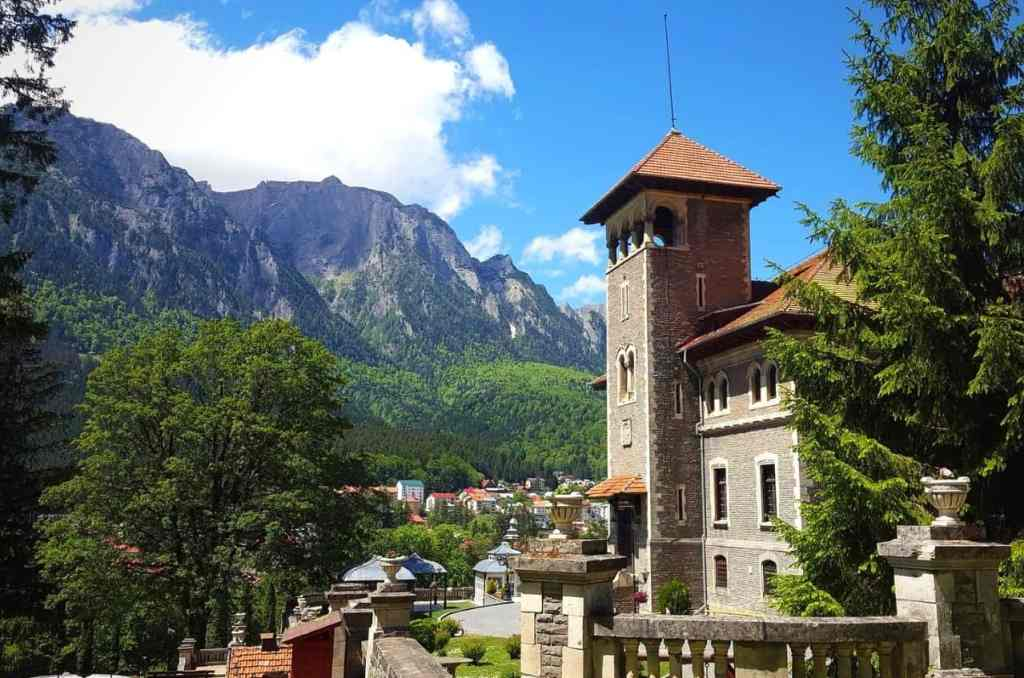 Cantacuzino Castle in Transylvania with mountains and clouds in the background.