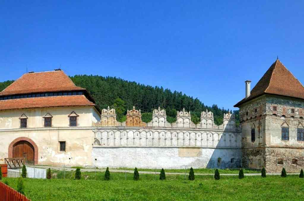 Red roofs and white outer facade of Lazar Castle, one of the most incredible Transylvanian castles to visit.