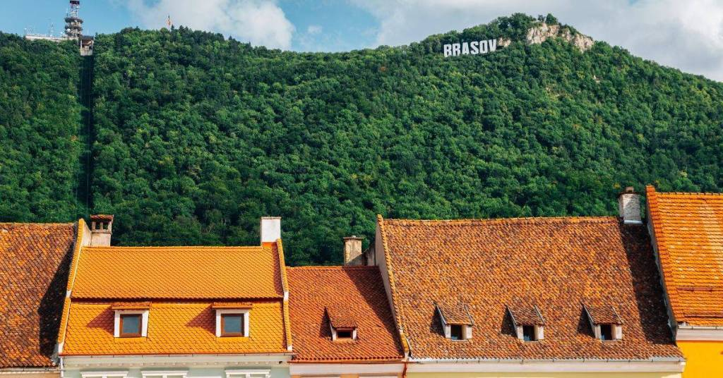 'Hollywood' Brasov sign seen in the trees on Tampa Mountain, Brasov with red roofs beneath the mountain.