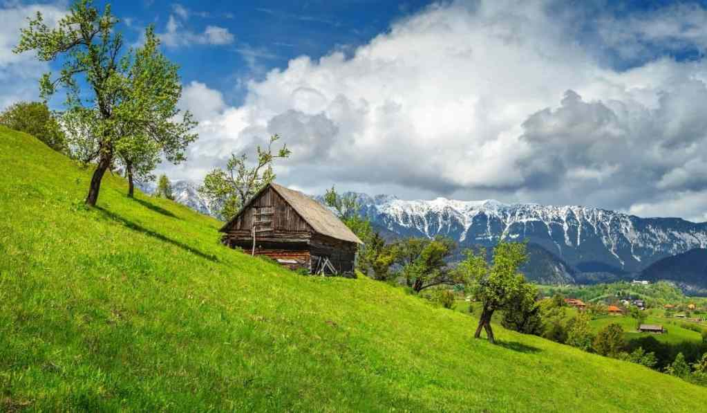 Transylvania landscape with wooden cottage on a hill in the mountains with lush green grass and cloudy skies.