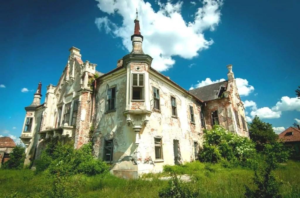 Teleki Castle under blue, cloudy skies in Transylvania, Romania.
