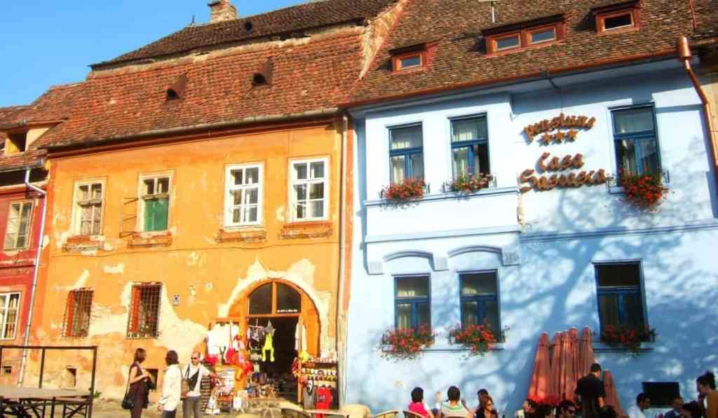 Colorful orange and blue storefronts in Sighisoara, Transylvania, Romania.
