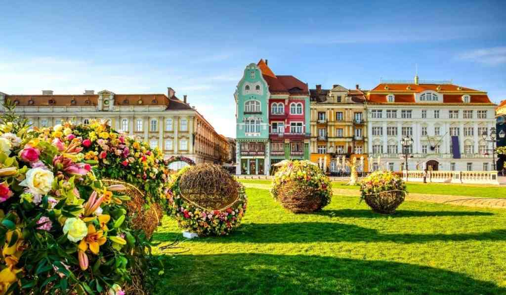 Piaţă Unirii in Timisoara, showcasing lots of flowers and Baroque and Secessionist architecture - one of the best things to do in Timisoara.