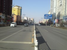 Crossing Chang An Lu, where factories fetch Directors and laborours with luxury busses.