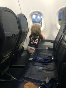 Toddler looking out airplane window on Spirit Airlines