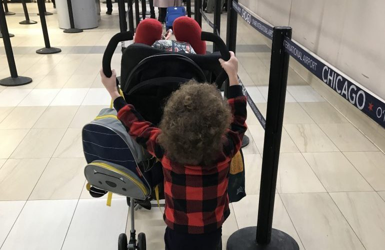 Navigating Airport Security with Children-toddler pushing stroller through airport security
