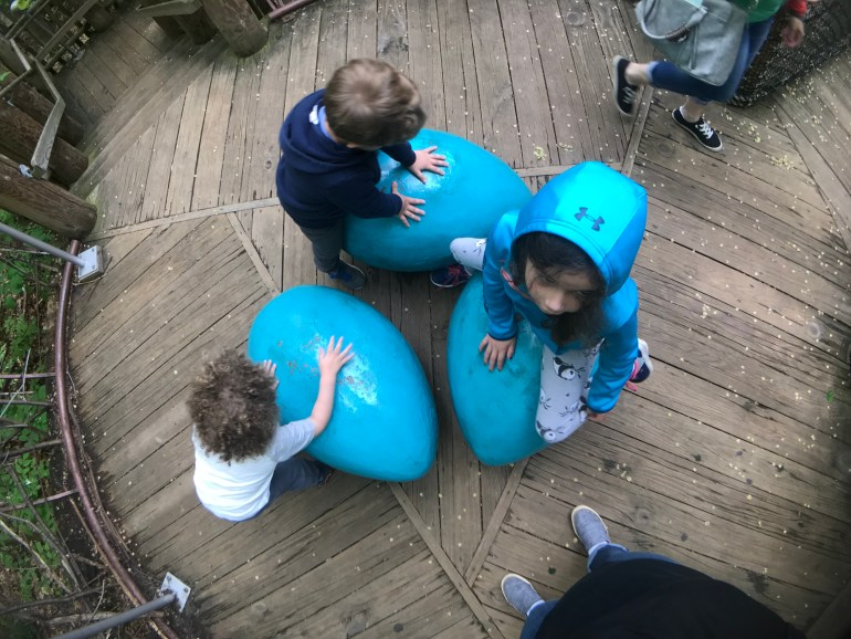 Children playing on blue eggs at the Treehouse Village exhibit at the Frederic Meijer Gardens and Sculpture Park