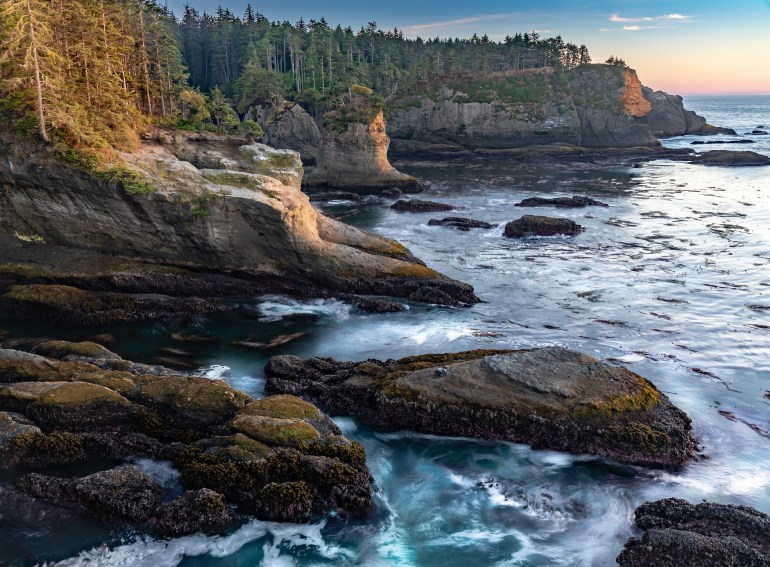 Overlook of Cape Flattery, with dramatic cliffs and pine trees in the background with rough, blue water in the foreground.