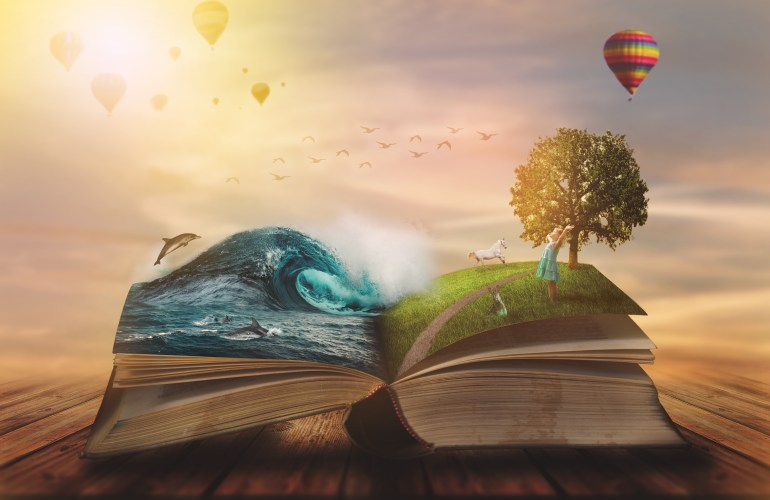 Book with ocean and grass errupting from the pages, with hot air balloons in the backgroun